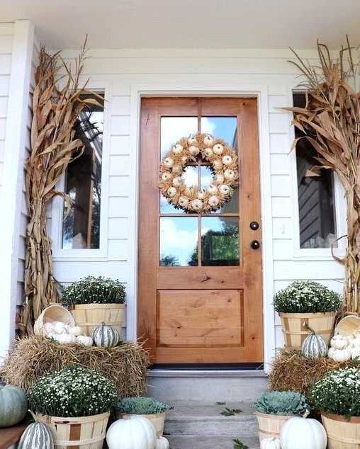 Fall front porch decorated with neutral pumpkins and greenery