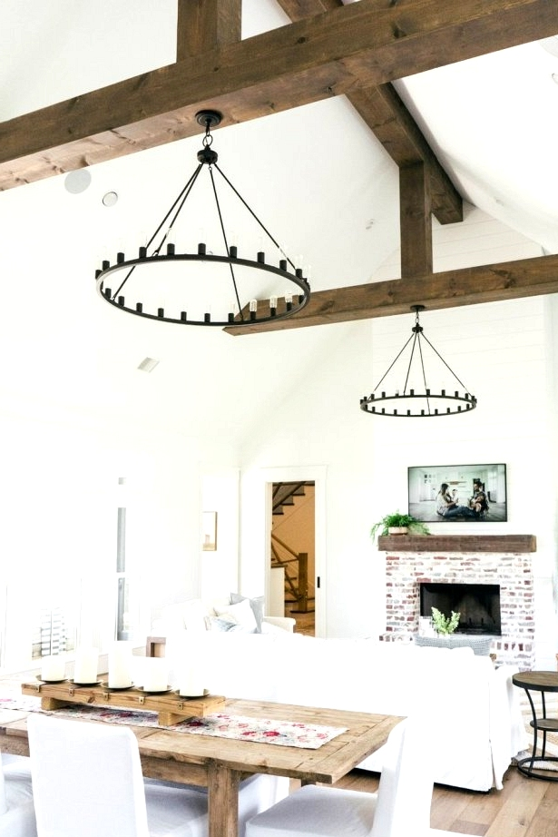 A farmhouse great room with a modern twist! Bold rustic beams and hoop lighting are the showstoppers of this farmhouse living room.