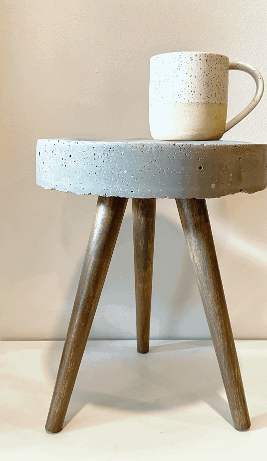 Industrial mid century inspired accent table with a cement top and grey stained wood legs.