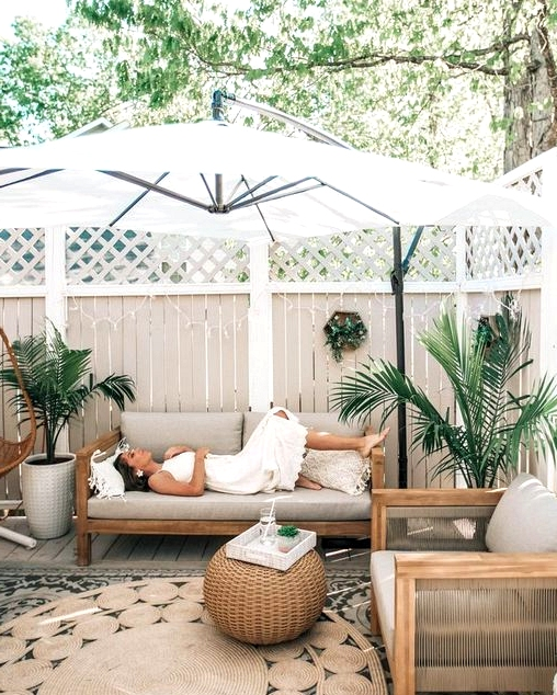 Relaxing backyard patio design with a large umbrella that provides much needed shade.