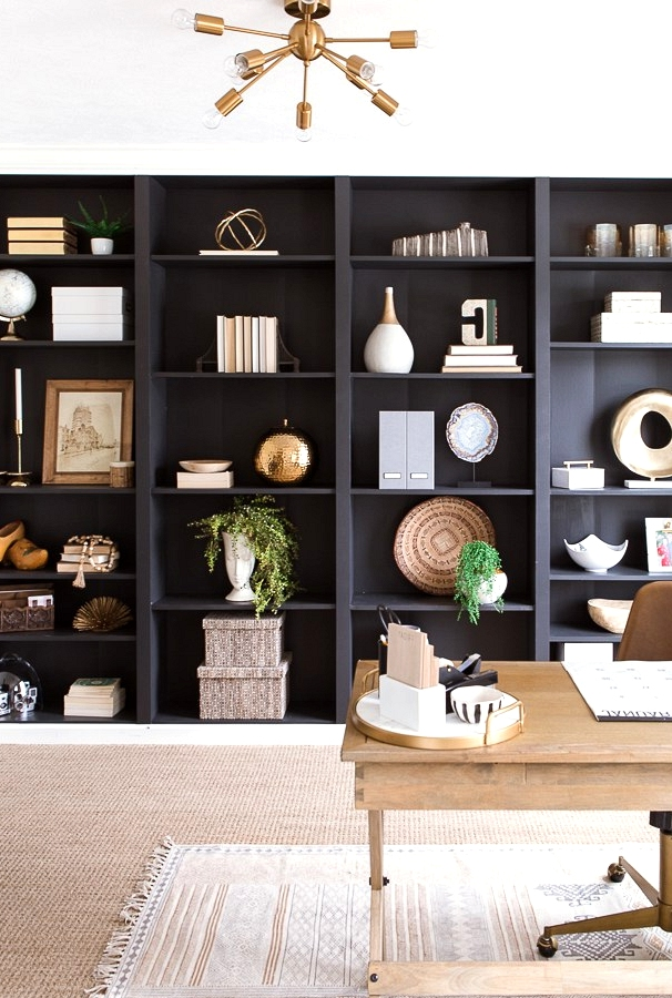 Black bookshelves create a feature wall in this modern home office.