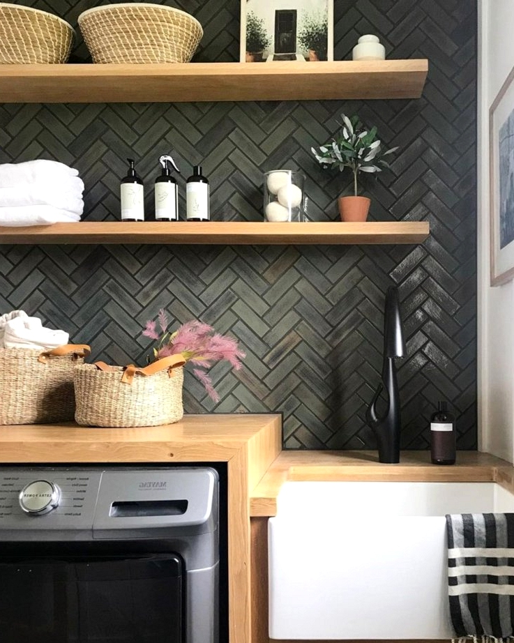 Moody herringbone tiles are the main feature of this beautiful laundry room design idea.