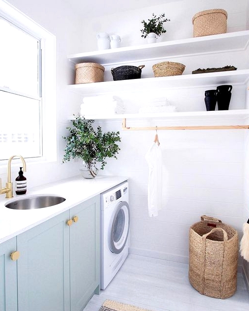 serene oasis laundry room with aqua cabinets and bright white paint