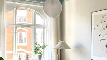 Blue stucco ceiling, library and posters: stylist condominium in Denmark