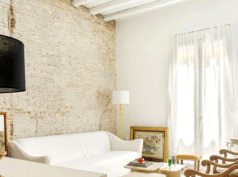 White studio house with brick wall and vintage armchairs in Barcelona (60 sqm)