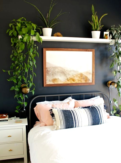 A beautiful boho bedroom with a black accent wall.