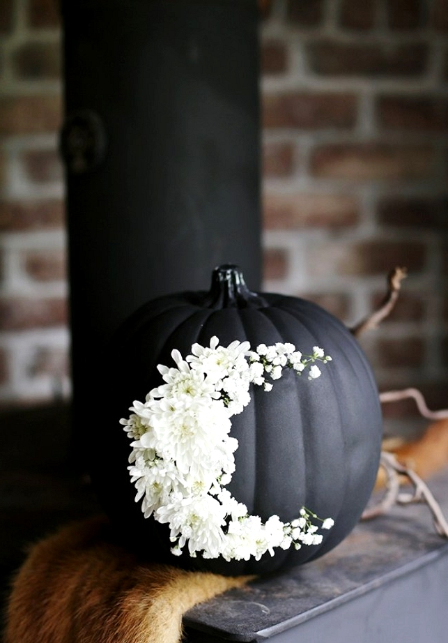 Painted black pumpkin decorated with fresh flowers.